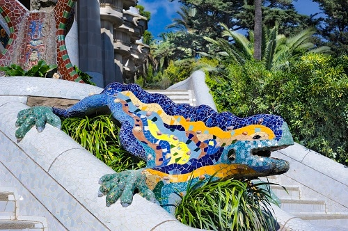 a colorful lizard statue on the steps of park guell