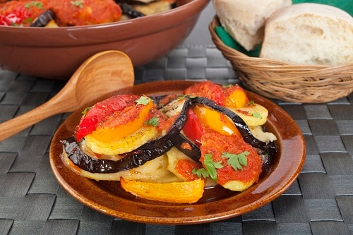 a dish of tumbet with some bread on the side