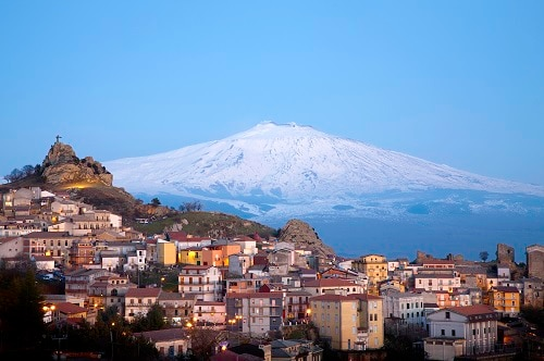 a panoramic view of mount etna overlooking a village
