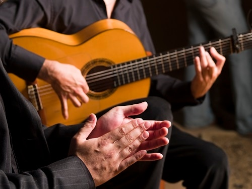 a man playing flamenco music on a guitar while another man claps along