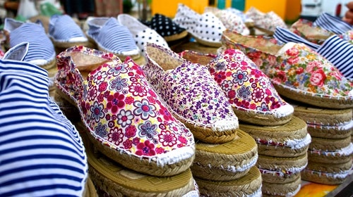 a set of floral espadrilles on display in a barcelona market