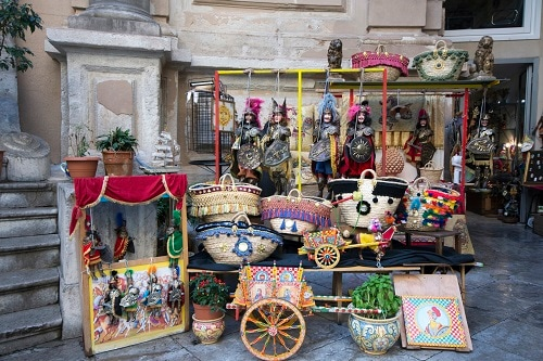 a souvenir cart with handbags and puppets in palermo, italy
