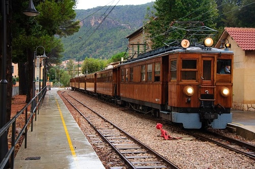 a vintage train passing through a station in the town of soller
