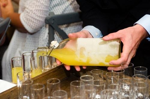 a waiter pouring a glass of limoncello