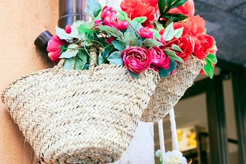 coffa bags hanging on a wall with pink and red flowers in them