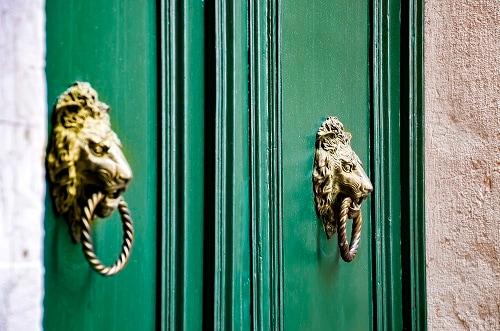 door knockers on the doors of a building in italy