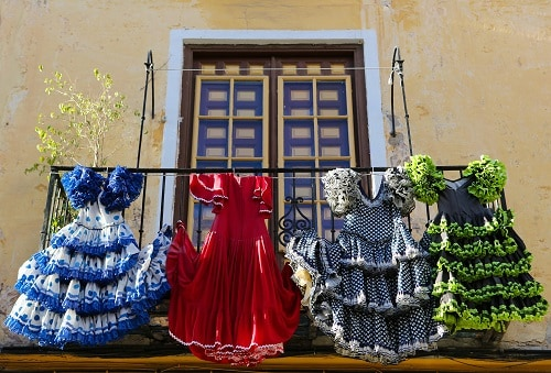 four flamenco dresses hanging from a balcony in malaga
