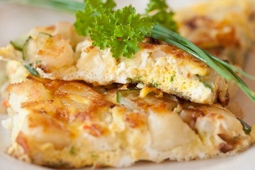 a close-up of tortilla de patata, or spanish tortilla with potatoes, with cilantro