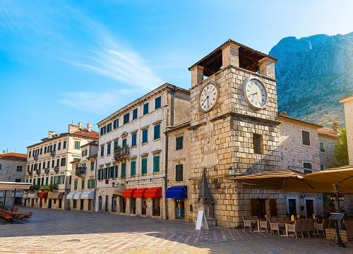 a giant clock tower and shops in old town kotor