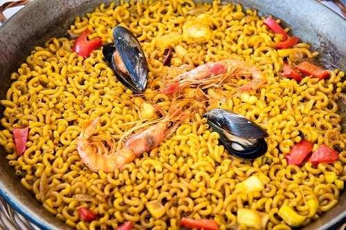 a pan full of fideua, a type of paella that is cooked with pasta instead of rice