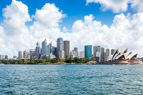 a wide view of the sydney city skyline with the sydney opera house