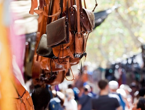 handmade leather bags hanging in an outdoor market in Inca, Mallorca