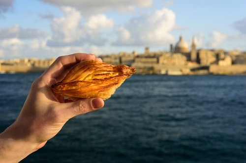 a person taking a picture of a maltese pastry