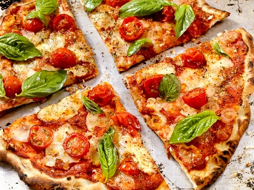 a pie of pizza margherita cut into four pieces