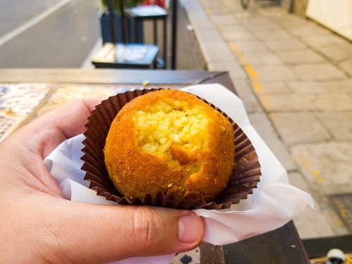 a tourist taking a bite of an arancine on the street
