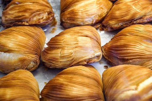 a tray of sfogliatelle on display at a bakery