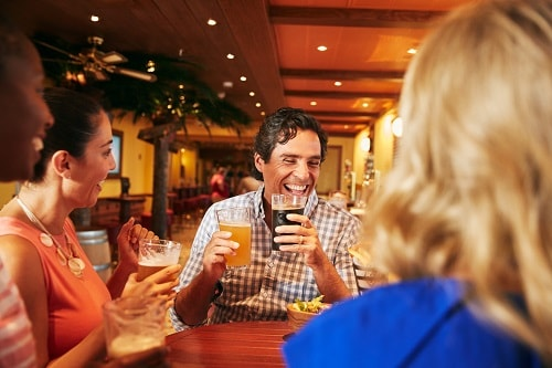 group of people laughing and drinking beer at the redfrog pub
