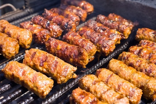 grilled cevapi, or minced meat sausages, being cooked on a grill