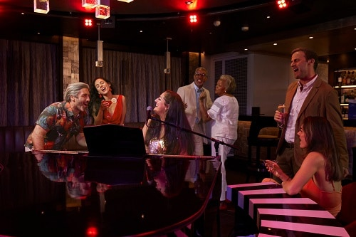 group of people singing at the piano bar