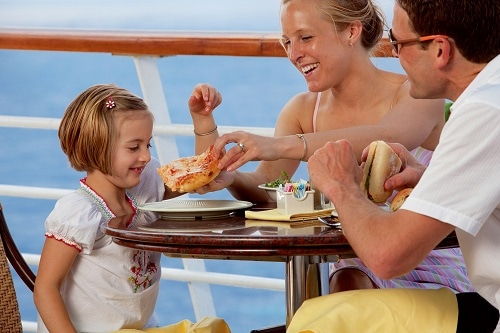 little girl eating pizza on a cruise ship with her family