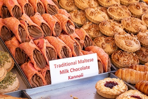 traditional maltese milk chocolate kannolis and other malta treats on display at a bakery in malta