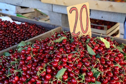 a large display of cherries for sale at a market in croatia