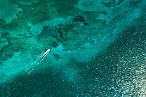 aerial view of a boat on the sea green waters of grand cayman