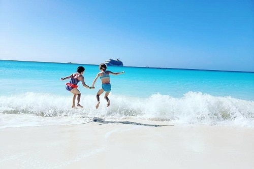 : two kids jumping over waves with a carnival ship in the backgroun