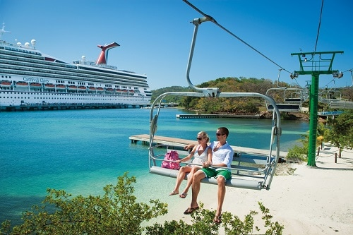 a couple riding the magical flying beach chair in mahogany bay