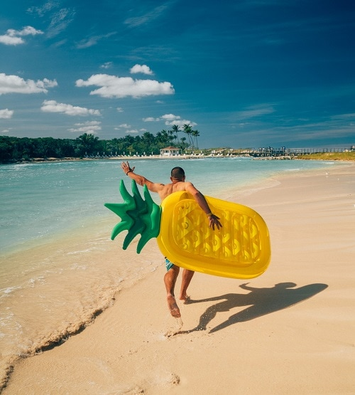 man carrying a pineapple floaty to the beach in nassau