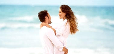 a couple dressed in white hugging on a beach