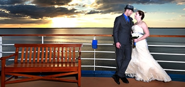 a newlywed couple posing for photos after their wedding on a carnival cruise with the sun setting in the background