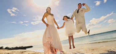 a couple and their daughter jumping after a wedding ceremony on a beach