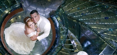 a newlywed couple posing for a photo next to a spiral staircase on a carnival cruise