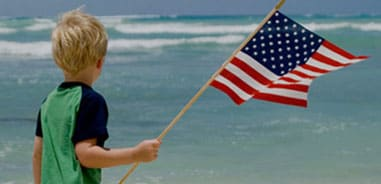Military Deals: KID HOLDING AN AMERICAN FLAG ON A BEACH