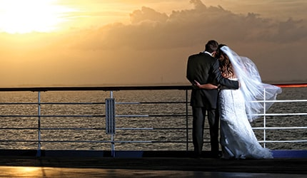 a couple on a cruise ship deck at sunset