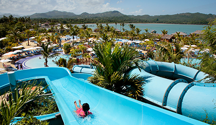 two guests zip lining over swimming pools and the ocean in amber cove