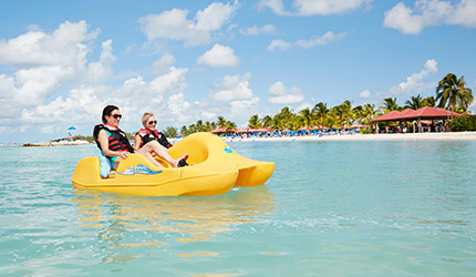 two ladies on a pedal boat in the crystal blue waters of princess cays