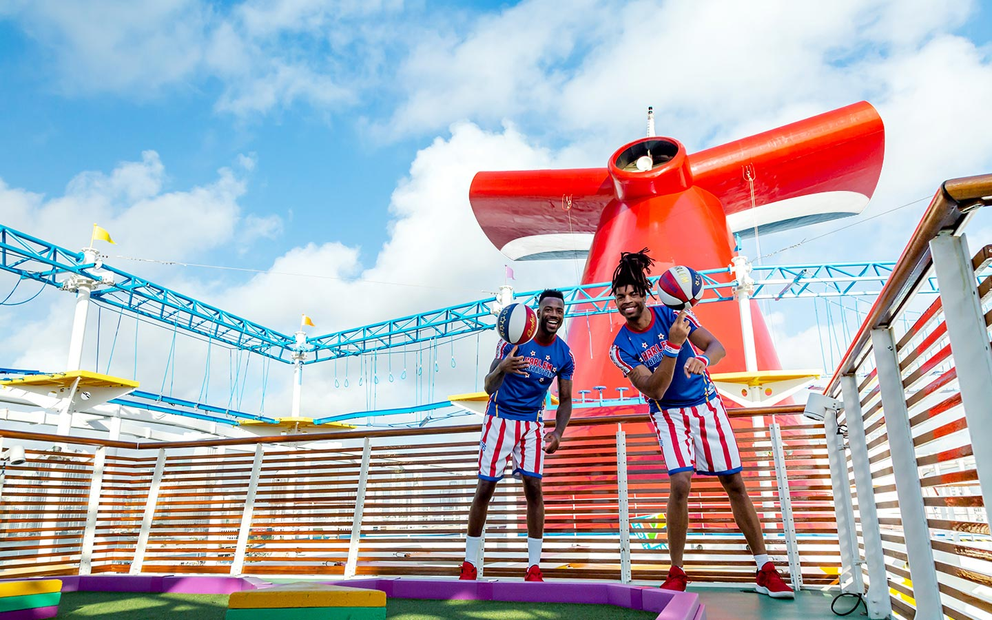two harlem globetrotters spin basketballs on carnival horizon