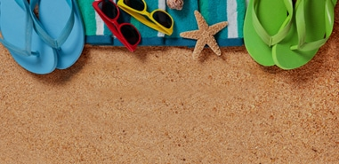 COLORFUL FLIP FLOPS LAYING ON A TOWEL AT THE BEACH