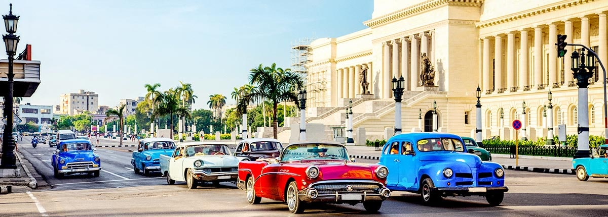 view of iconic cars driving on cubas capital street