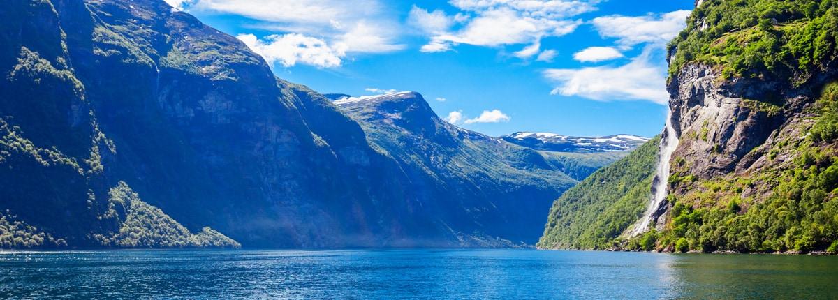 a blue fjord is greeted by mountains full of plant life