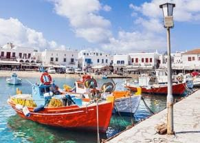 colorful wooden boats along the pier in mykonos, greece