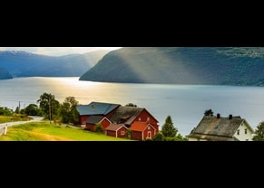sunrays beam down on a red and white barn house located off the shoreline of a fjord