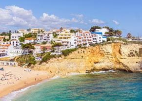 beautiful carvoeiro with colorful houses by beautiful, sandy beach