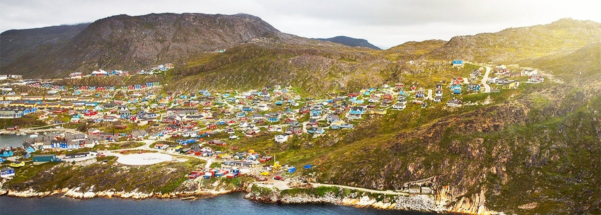 view of the city of qaqortoq nestled among the mountains
