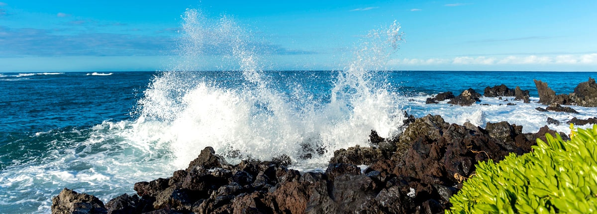 waves crashing into the rock lined coastline in kona