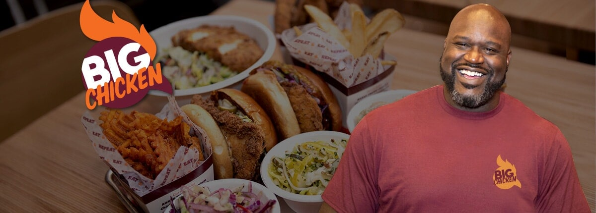 shaq and the big chicken logo are showcased with large chicken sandwiches, fries and side dishes