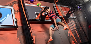 kid playing basketball at sky zone on carnival panorama