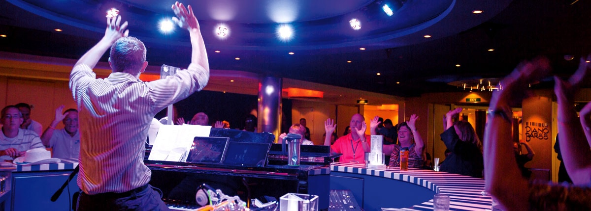 order your favorite cocktail and sing along at piano bar on carnival cruise line